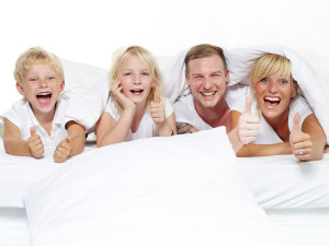Parents have fun with kids in bed